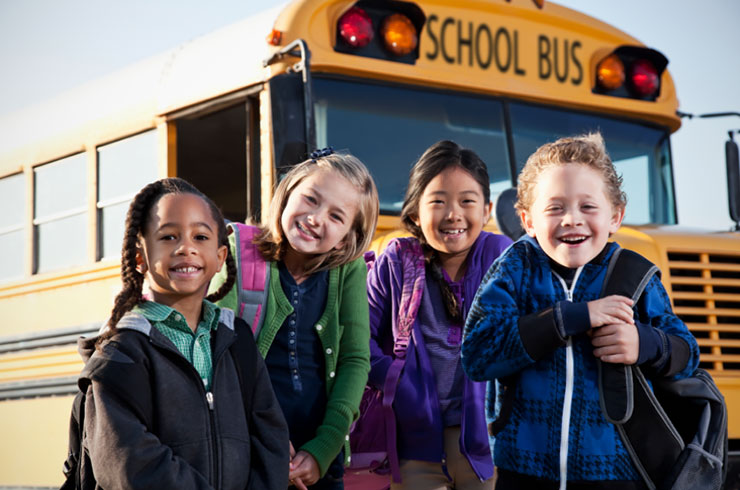 Kids waiting in front of school bus.