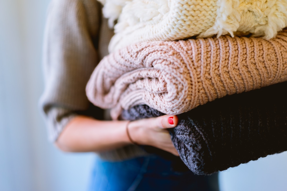 Woman holding sweaters, seasonal clothes storage