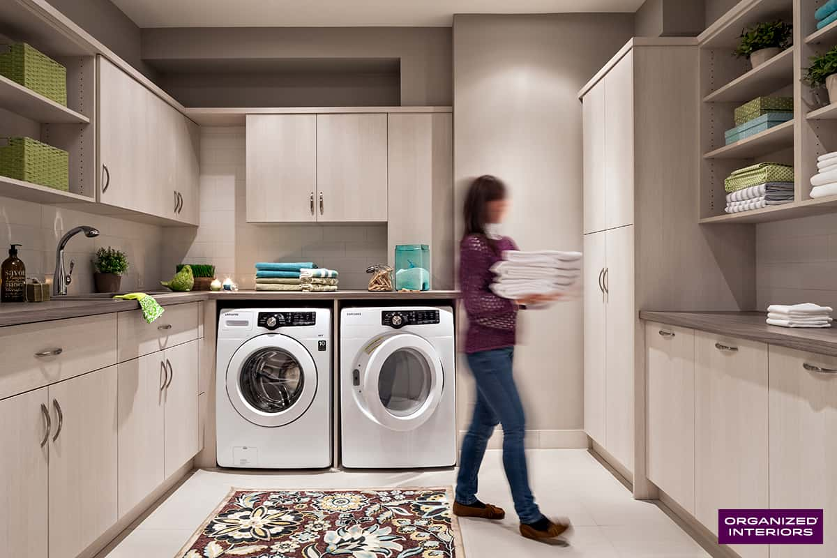 woman carrying linens past washer and dryer