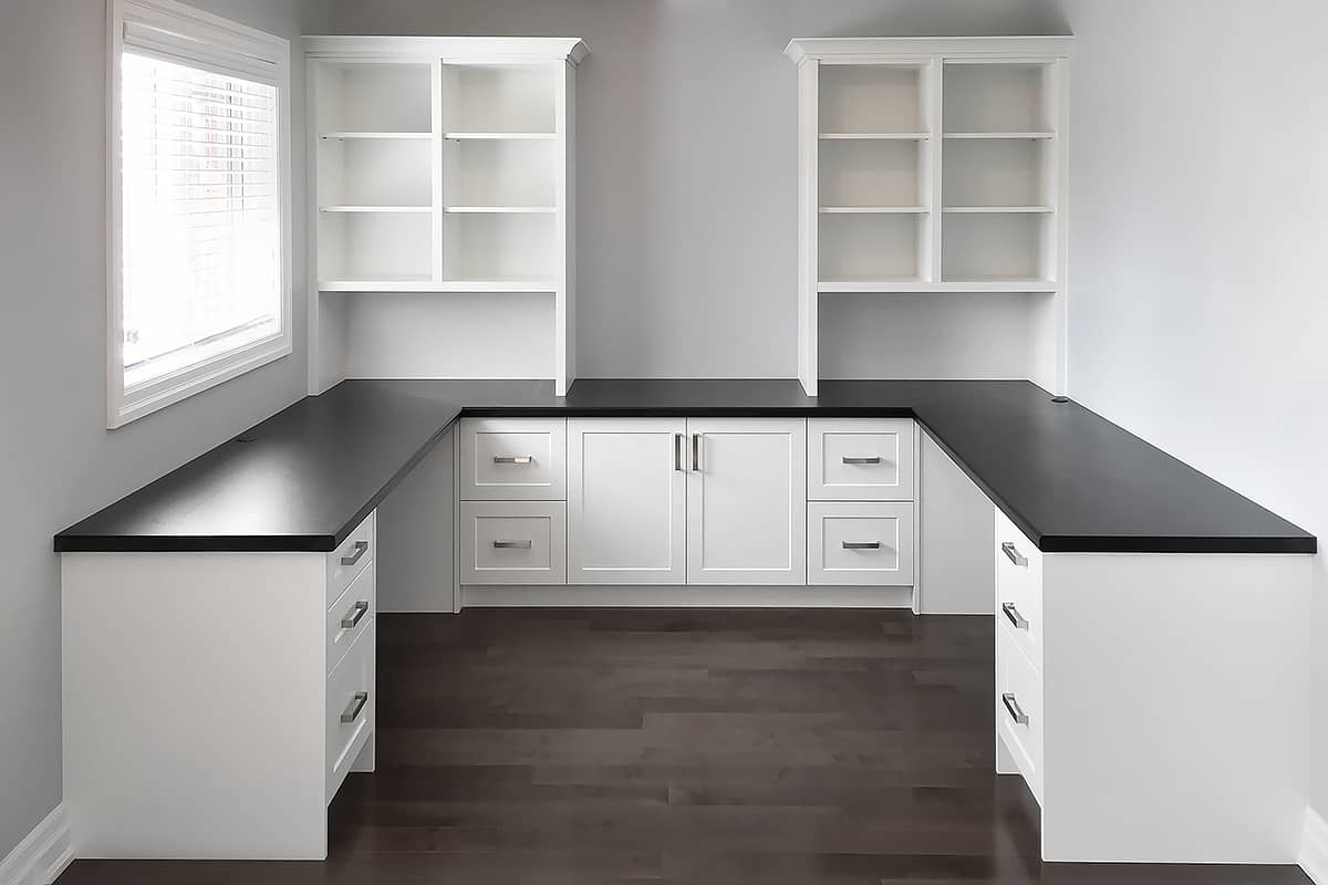 new unfurnished home office with white cabinets and black desktop