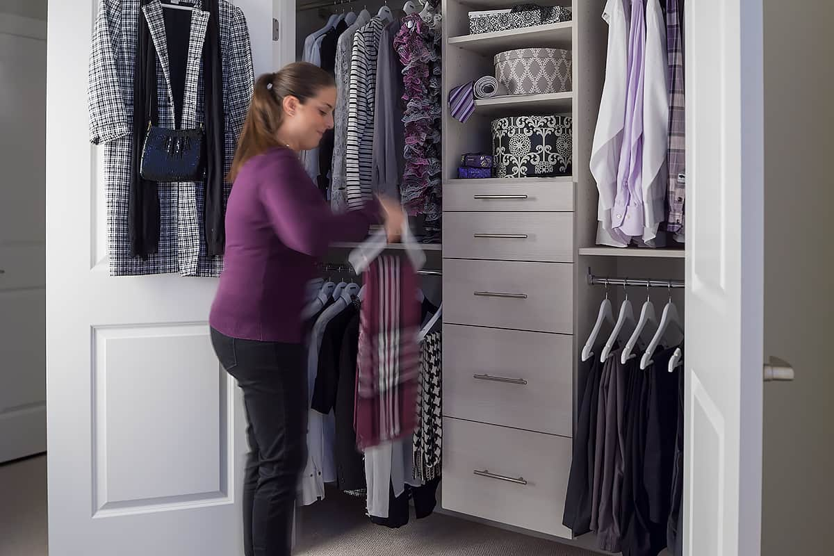 woman sorting clothes in reach-in closet