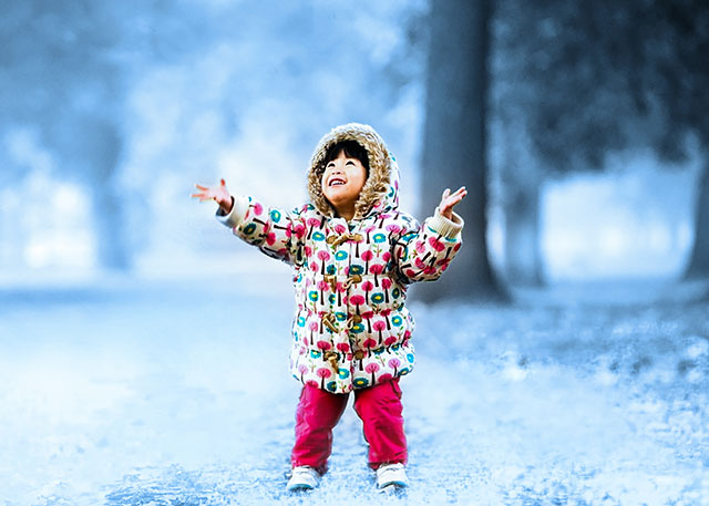 Child with winter coat in park.